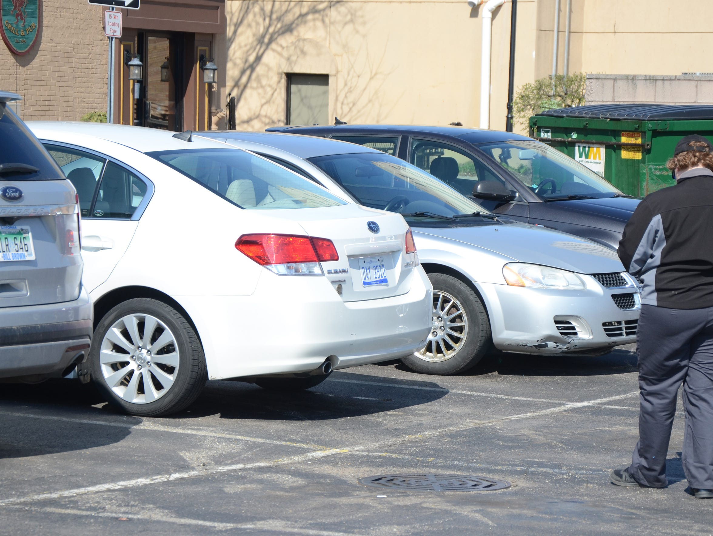 An employee of Ampco Parking checks cars in the State