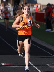 Silverton's Maddie Fuhrman smiles as she crosses the finish line in the 4000 meter relay on Friday, April 15, 2016, during the Vikings Relays Twilight Invitational track and field meet at North Salem High School.