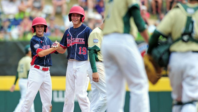 Mid-Atlantic Region second baseman Jude Abbadessa (3) high fives pitcher Ryan Harlost (19) in the fourth inning against the Asia-Pacific Region during the championship game of the 2016 Little League World Series at Howard J. Lamade Stadium at Aug. 28, 2016.
