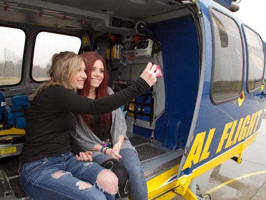 Friends Cheyanne Havermahl, left, and Kelsey Schmitz got a tour of not only a Livingston County EMS ambulance like the one Schmitz was transported in after an ATV accident last year, but also got to sit in the University of Michigan Survival Flight helicopter as part of that tour. Havermahl provided not only emotional but critical emergency medical support for her friend in the minutes following the accident they both endured.