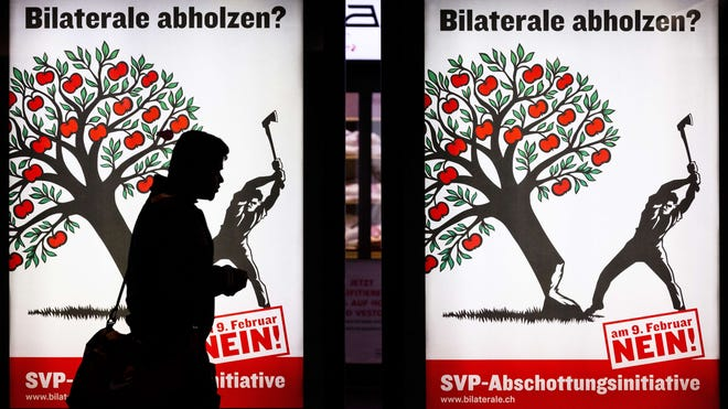 A man walks past posters asking voters to cast their ballot against an anti-immigration proposal on Feb. 6 in Zurich.