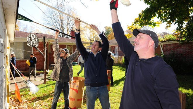 Mercy Road Church members Jamison Ortiz, Brad Davis and Dave Taylor clear a roof of leaves at a home on Salem during Make a Senior Smile Day this past Saturday in Redford.