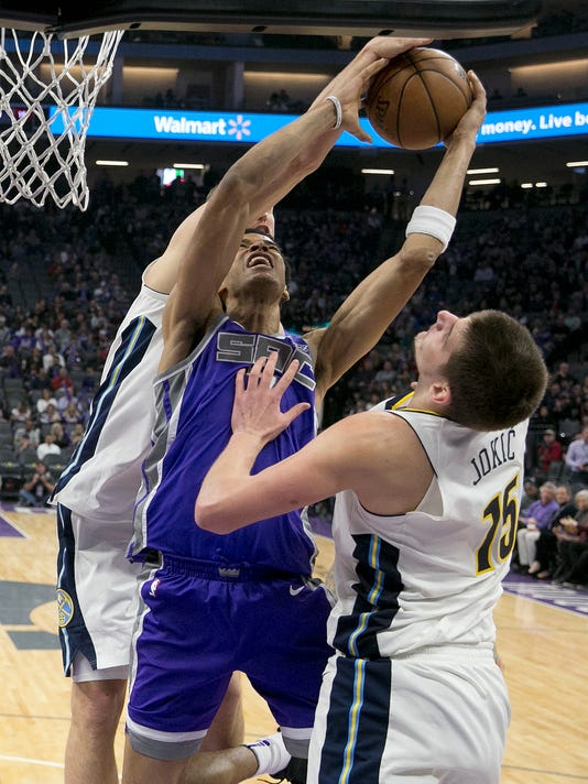 Sacramento Kings forward Skal Labissiere, center, goes to the basket between Denver Nuggets' Mason Plumlee, left, and Nikola Jokic during the second half of an NBA basketball game Saturday, Jan. 6, 2018, in Sacramento, Calif. The Kings 106-98. (AP Photo/Rich Pedroncelli)