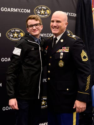 Pace High School student Chase Pellerin is photographed with his father Sgt. 1st Class William Pellerin on Monday during a ceremony to announce Pellerin's selection for the 2016 U.S. Army All-American Marching Band. Pellerin and 124 high school musicians from around the country were selected for the elite band to perform during the U.S. Army All-American Bowl on Saturday January 9, 2016 at the Alamodome in San Antonio, Texas.