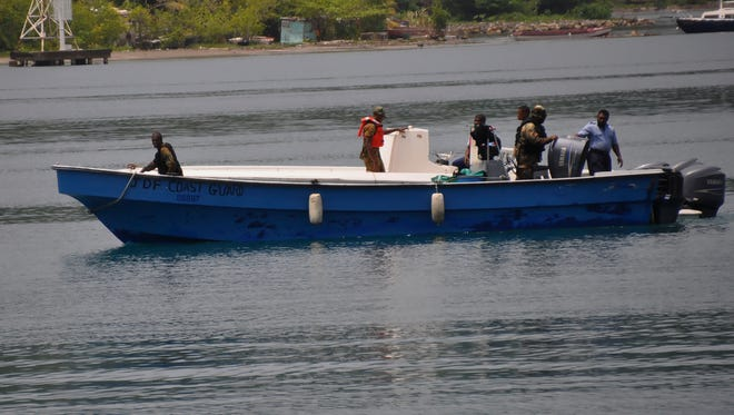 Jamaican Defence Force members return to Port Antonio Marina in Portland, Jamaica, Saturday, Sept. 6, 2014, after a fruitless search for the Glazers' plane.