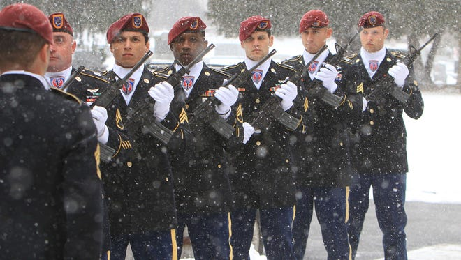 A military honor guard waits in the snow to fire a 21-gun salute following the funeral of U.S. Army Captain Clayton Carpenter into Shrub Oak United Methodist Church for his funeral service Jan. 25, 2014. Carpenter was killed when the Black Hawk helicopter he was flying crashed.