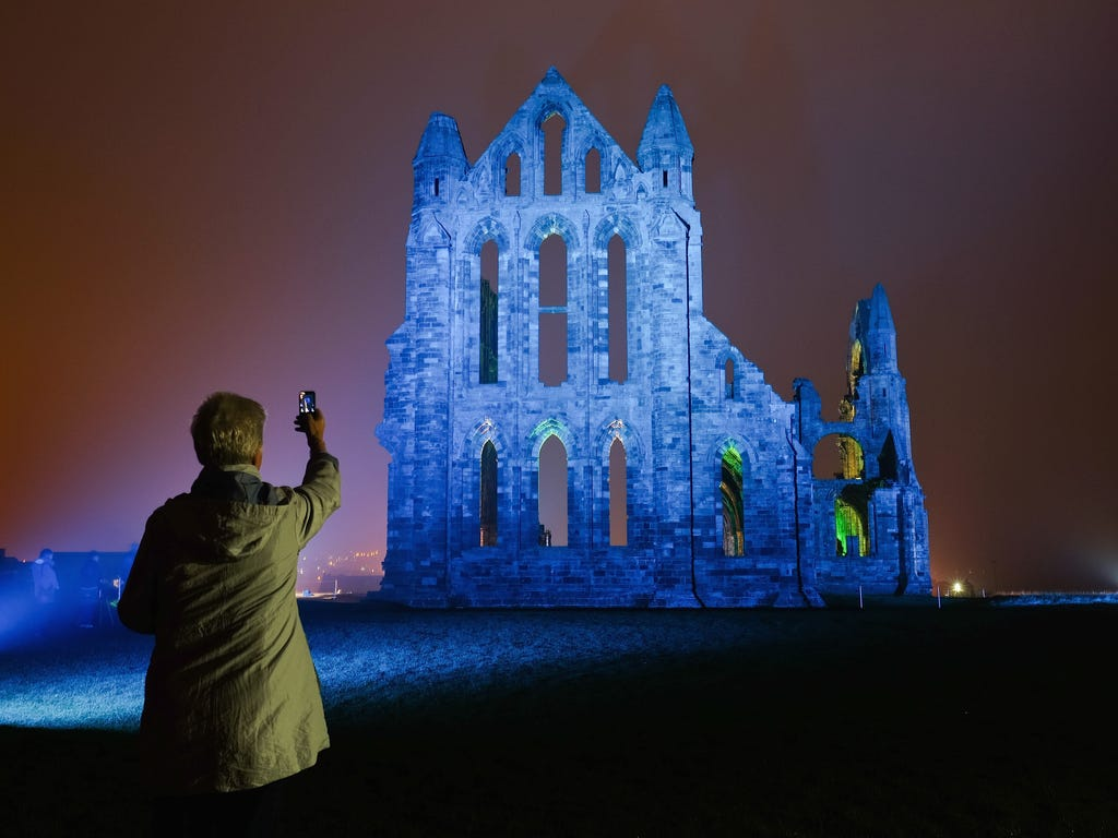 A woman takes a picture as a light display illuminates the historic Whitby Abbey in Whitby, England. The famous Benedictine abbey will be illuminated over four nights to coincide with Halloween and the popular Whitby Goth Weekend. The Abbey was part