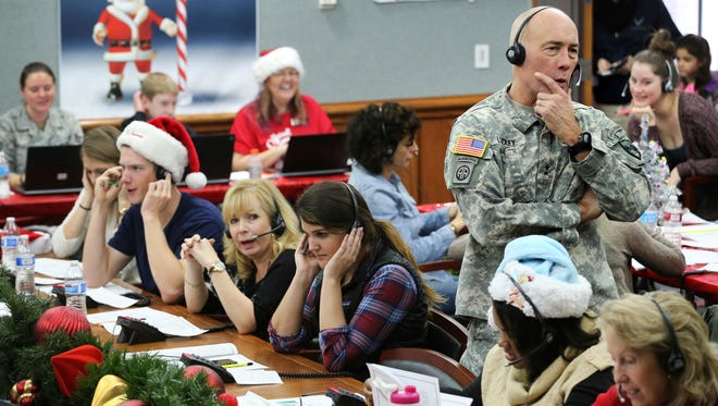 FILE - In this Dec. 24, 2014, file photo, NORAD and USNORTHCOM Chief of Staff Maj. Gen. Charles D. Luckey joins other volunteers taking phone calls from children around the world asking where Santa is and when he will deliver presents to their homes, inside a phone-in center during the annual NORAD Tracks Santa Operation, at the North American Aerospace Defense Command, at Peterson Air Force Base, Colo. Hundreds of volunteers are on the phones at the base, answering questions from eager kids who want to know where Santa is on his Christmas Eve travels.