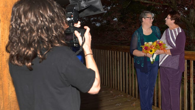 Laura Rich, left, takes a photo of April Miller, center, and Karen Roberts before they renew their vows in a public ceremony, Saturday, Oct. 24, 2015, in Morehead, Ky. Miller and Roberts were the plaintiffs in a suit filed against Rowan County Clerk Kim Davis by the American Civil Liberties Union in an attempt to have her office issue marriage licenses.