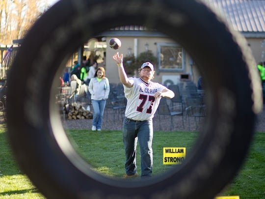 Owen-Withee football player Dustin Pecha, 18, throws a football through a tire at the Will Power fundraiser to benefit Will Maki at Munson Bridge Winery in Withee, Saturday, Oct. 17. Will Maki was diagnosed with osteosarcoma bone cancer in his femur in July and had to have his leg amputated in September. The tire toss was one of the games being played at the fundraiser.