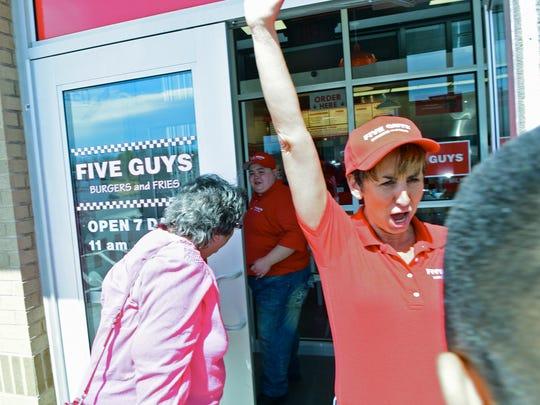 Judy Lekki welcomes customers at the new Five Guys burgers, fries and milkshakes restaurant Tuesday at 924 Norland Av., Chambersburg.