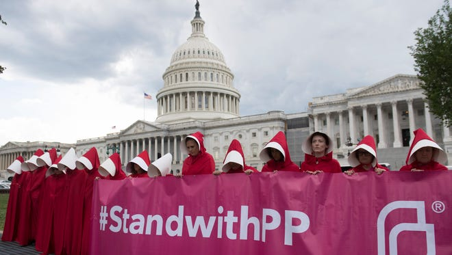 """Supporters of Planned Parenthood dressed as characters from """"The Handmaid's Tale,"""" hold a rally as they protest the US Senate Republicans' healthcare bill outside the US Capitol in Washington, DC, June 27, 2017."""