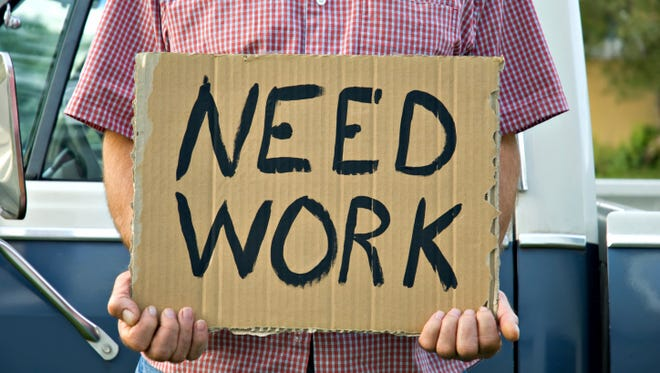 Man holding Need Work sign.