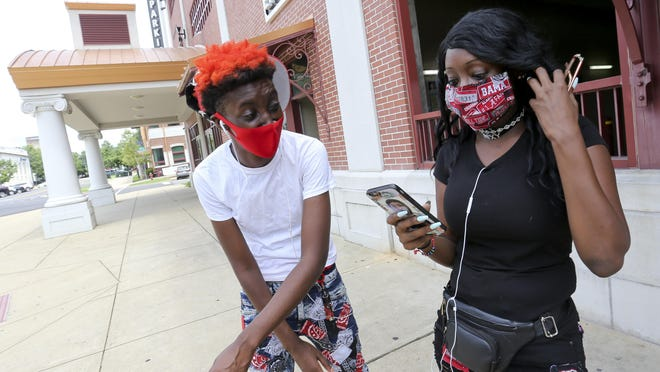 LaErica and Erica Brown wear face masks as they wait at the Tuscaloosa Intermodal Facility to catch a bus, Monday, July 6, 2020.