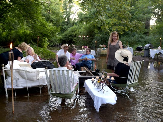 "Rachael McCampbell, right, host a party for friends in a creek behind her Leiper's Fork, Tenn. home on July 16, 2016. Outdoor chairs and tables are placed in the water for the  ""creek party"".  ""I think the best way to fully enjoy the creek is to actually pull a chair out in the middle and sit there beneath the trees with your feet in the water. Whenever I have company, and the weather is warm enough, I like to put furniture in the creek and enjoy the environment that way. It's definitely a lot more work to bring down food, grills, chandeliers, tablecloths, candelabras, the fire pit etc. and put them in the creek. But the end result is worth it when you see your guests' faces light up,"" said  McCampbell."
