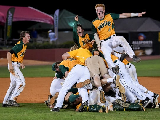 Saint Xavier teammates celebrate after defeating Highlands High School to win the Kentucky state baseball championship at Whitaker Bank Ballpark in Lexington, Ky, June 16, 2018.