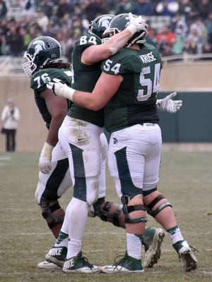 Senior Connor Kruse (54) gets a hug from teammate Andrew Gleichert (84) after he took a handoff and ran the football for a gain of 1-yard late in the game.