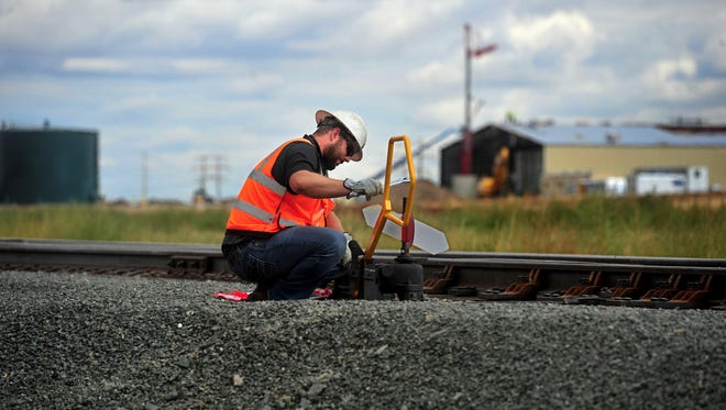 Casey Pardun of the company Railworks adjusts a railroad switch on the rail spur that will service the Great Falls AgriTech Park on 18th Ave N.