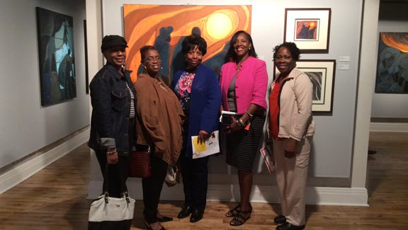 """Teniade Broughton, of the African-American Heritage Society (AAHS), and Dr. Eurydice Stanley take in the sights with their children (who are members of the AAHS's children's program)  at """"Our Voices Are Many"""" performance with """"Color in Freedom"""" exhibit."""