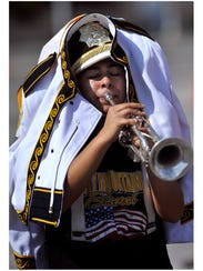Trying to protect herself from the hot sun, Santa Anna High School junior Kloey Guerrero practices with her trumpet. The Mighty Mountaineer Marching Band was rehearsing on Nov. 6, before the finals of the Class 1A UIL State Marching Contest in San Antonio.