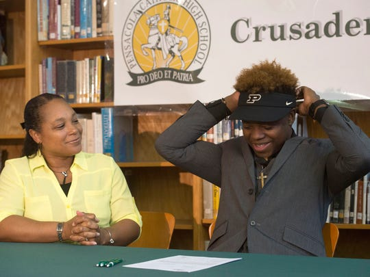 Catholic High School standout Simeon Smiley, right, shows off his Purdue colors after committing to the university on National Signing Day, while his mother, Sybil, left, looks on Wednesday morning Feb. 3, 2016.