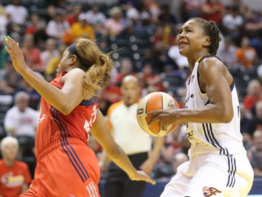 Tamika Catchings evades a defender and heads for the basket. The Indiana Fever hosted the Washington Mystics in WNBA playoff action at Bankers Life Fieldhouse Thursday August 21, 2014.