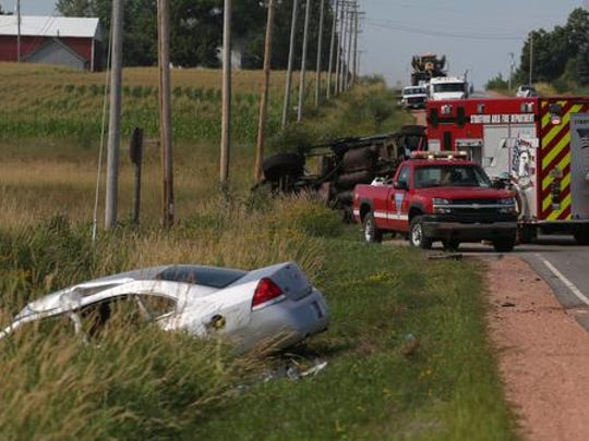 A silver Chevrolet Impala rests in the ditch at the scene of an accident at the intersection of County M and Maple Street, 2 miles south of Rozellville, in the town of Day, Monday, July 27. It collided with a heavy-duty truck, background, which can be seen lying on its side.
