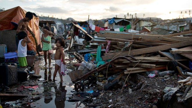 A family stand among debris in Tacloban in the Philippines on Sunday.