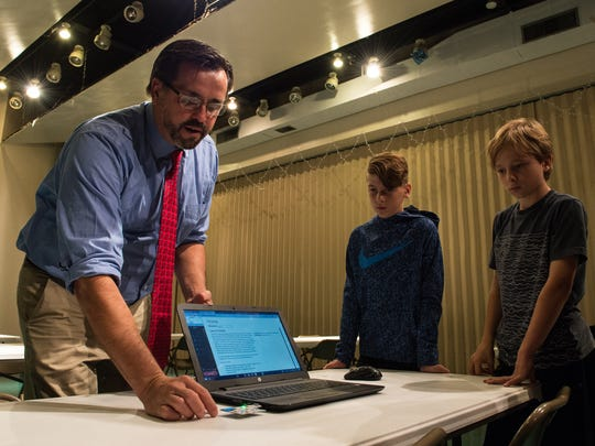 Snow Hill Middle School science teacher Everett Evansky shows students Conner Elliott, left, and Sage Labesky how an xChip works on Tuesday, Oct. 17, 2017.