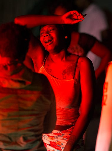 A young woman mourns at the scene of a shooting that left three dead and four injured on Genesee St. early in the morning on Thursday, August 20, 2015.