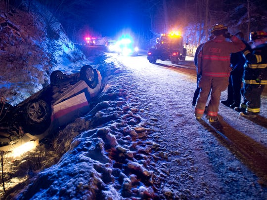 January 2014: Rescue crews wait for a tow truck to remove a vehicle from a small creek off Lamore Road in Essex after the driver lost control, rolling onto the roof and partially submerging him. Quick thinking by another motorist resulted in a quick response by emergency crews.