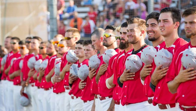 Palm Springs Power team stand holding their baseball caps during the National Anthem
