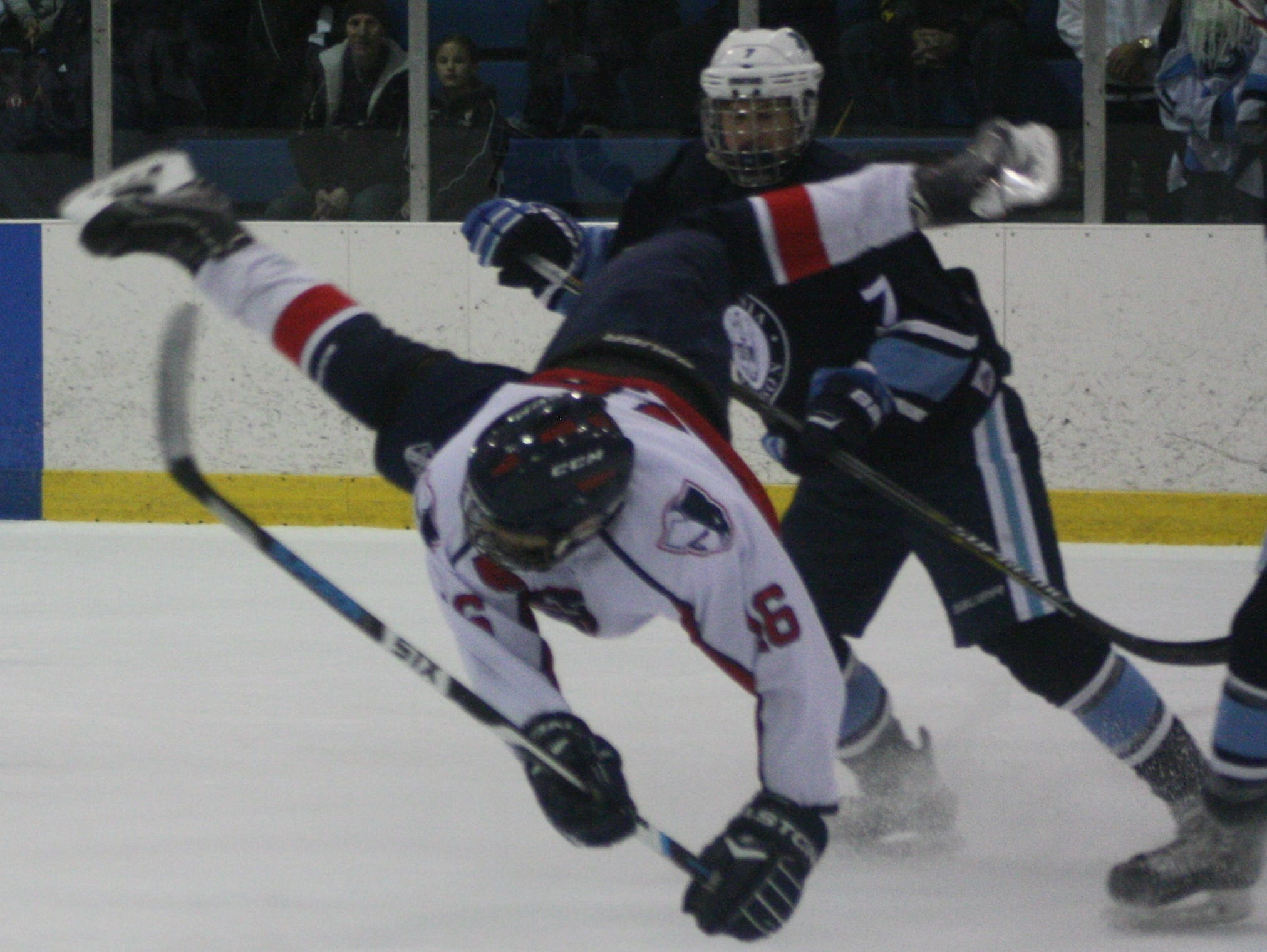 Livonia Franklin forward Chase Wallis gets upended following a first-period collision with Stevenson goalie Cullen Barber.