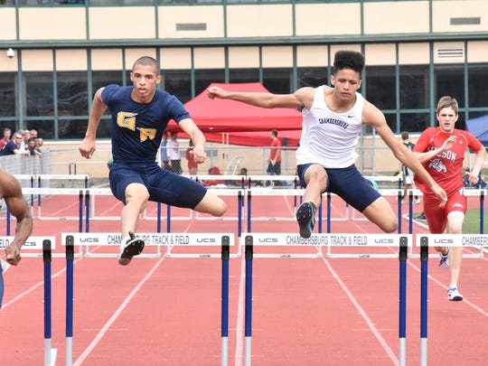 Greencastle's Darius Carter (left) and Chambersburg's Trayton Barnette (right) compete in the 300 hurdles at the 12th annual Tim Cook Invitational at Chambersrburg on Saturday, March 25, 2017.