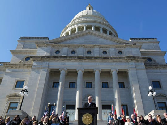 Arkansas Gov. Asa Hutchinson, center, gives his inauguration address on the steps of the Arkansas state Capitol in Little Rock on Tuesday.