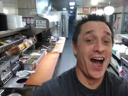 Alex Bowen poses in the kitchen at a Waffle House in West Columbia, S.C. When Bowen found the only worker at the eatery asleep, he took his meal into his own hands. Bowen chronicled with selfies how he made his own double Texas bacon cheese steak melt on Facebook.