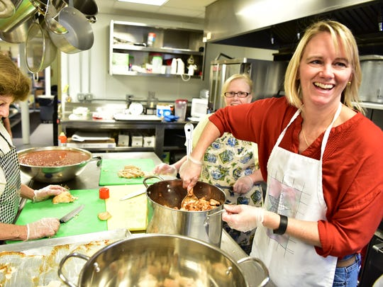 Meals with a Mission volunteer Jen Hollenbaugh, right, jokes with co-workers while  preparing meals for the homeless in Garfileld, on November 4. So far the non-profit has cooked over a half of million meals since they started working six years ago.
