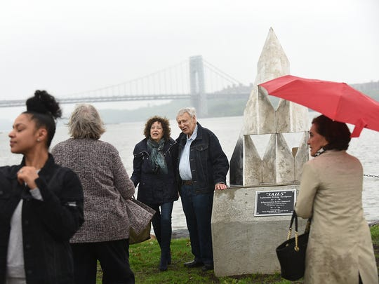"""Dedication of the Ephraim Peleg sculpture """"Sails"""", on Wednesday, May 16 2018 at Veterans Field in Edgewater. A woman takes a selfie as Peleg poses for photos in front of the recently unveiled statue."""