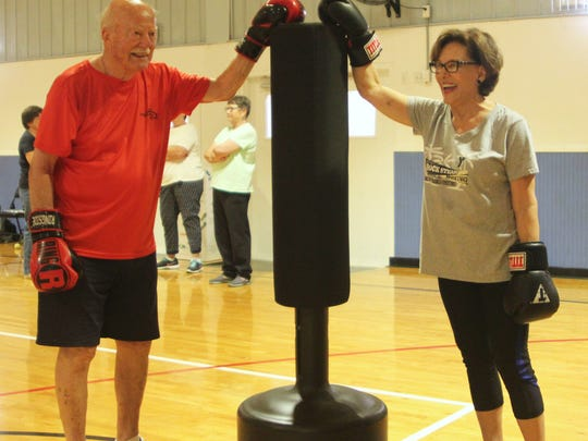 Program participant R.J. Brockmann, 90, and volunteer helper Sharon Lewis take a breather after an energetic session on the punch bag.