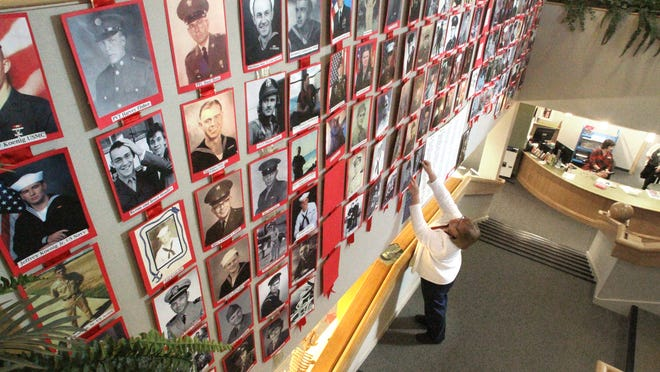 Howell Archives volunteer Joyce Fisher posts more than 60 photos of veterans and active duty service members on a wall at the Howell Carnegie District Library. Fisher hopes to eventually post 100 images in time for Veterans Day celebrations. The display features shots of male and female veterans from the Civil War through current duty.