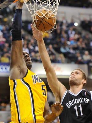 Roy Hibbert dunks over Brook Lopez of the Nets.
