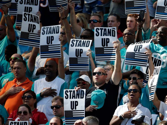 FILE - In this Nov. 27, 2016, file photo, fans show how they feel about players that don't stand for the National Anthem, during the first half of an NFL football game between the Miami Dolphins and the San Francisco 49ers in Miami Gardens, Fla. The anthem is played before the start of every U.S. major sporting event, where fans and players are expected to salute the flag by placing a hand over the heart while singing along. Not doing so is considered unpatriotic by some. The anthem has also been used by athletes as a way to protest. (AP Photo/Lynne Sladky, File)