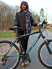 Johara Arbow poses with her shiny Trek bicycle, which she received as a donation after her first bike was stolen.