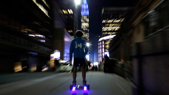 FILE - In this Oct. 21, 2015, file photo, a young man rides a hoverboard along a Manhattan street toward the Empire State Building in New York. Several Utah universities are joining colleges around the country in restricting hoverboards on campus, as federal officials review dozens of fires tied to the self-balancing scooters. (AP Photo/Kathy Willens, File)