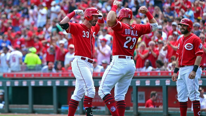 Cincinnati Reds right fielder Jesse Winker (33) reacts with left fielder Adam Duvall (23) after hitting a three run home run against the Chicago Cubs in the seventh inning at Great American Ball Park on Sunday, June 24, 2018.