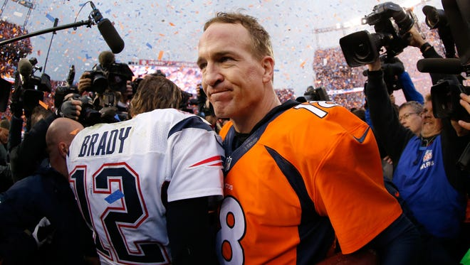 Peyton Manning, right, of the Denver Broncos and Tom Brady of the New England Patriots meet after the AFC championship game at Sports Authority Field at Mile High on Jan. 24, 2016, in Denver.