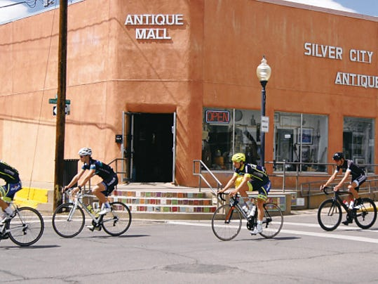 Bikers ride past the Antique Mall on Broadway Street on Tuesday. Racers were in town days before the Tour of the Gila began.