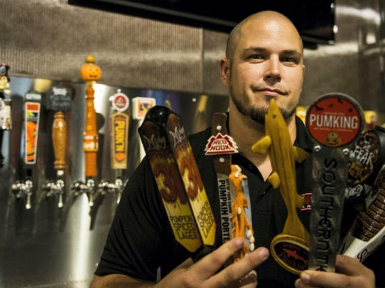 "Chris Viozzi, assistant general manager at Funck's Restaurant in Palmyra, holds several pumpkin beer tap handles as the restaurant prepares to have a ""Pumpkin Wars"" event on September 10th at 6:30 p.m. The restaurant currently has 20 pumpkin beers on tap and expect to have another five to 10 on tap by the event, according to Chris Viozzi, assistant general manager."