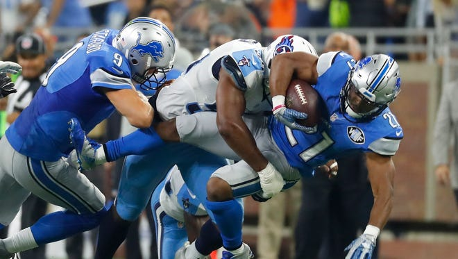 Lions running back Ameer Abdullah is tackled by Titans linebacker Avery Williamson while Lions QB Matthew Stafford blocks during the first half Sunday, Sept. 18, 2016, in Detroit.