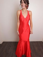 Model, Sophie Puente wearing a red dress from Soirée Couture ($450) with red earrings ($59) and a gold bracelet ($29) both from Stacey's.